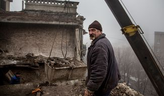 In this photo taken on Wednesday, Feb. 3, 2016, a construction worker removes rubble from the roof of a severely damaged condo in Debaltseve, eastern Ukraine. Money from Russia helps to the rebuild eastern Ukrainian town of Debaltseve, a strategic rail hub that rebels pounded for weeks before driving out the government troops a year ago. But there has been little or no money to spare for the nearby villages, which still bear the scars of one of the fiercest battles of the war. (AP Photo/Petr Anikukhin)