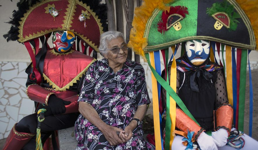"""""""Caretas"""" performers sit next to an elderly woman during Carnival celebrations in Triunfo, Brazil, Monday, Feb. 8, 2016. Revelers take to the streets in hand-made costumes that feature huge hats, long whips _ and scowling masks.  (AP Photo/Felipe Dana)"""