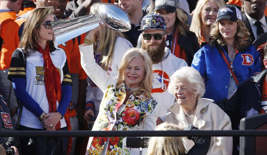 Annabelle Bowlen, left, wife of Denver Broncos owner Pat Bowlen, holds up the Lombardi Trophy while her mother, Joan Spencer, looks on at a rally following a parade through downtown Tuesday, Feb. 9, 2016 in Denver. Fans crowded into Denver's downtown to salute the Broncos for the team's victory over the Carolina Panthers in Super Bowl 50. (AP Photo/David Zalubowski)