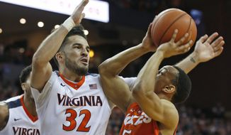 Virginia guard London Perrantes (32) smothers Virginia Tech guard Justin Robinson (5) during the first half of an NCAA college basketball game in Charlottesville, Va., Tuesday, Feb. 9, 2016. (AP Photo/Steve Helber)