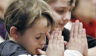 6 year old Gavin Price follows the lead of big sister Sydney Price, 11, and prays during Ash Wednesday service at St. Rose of Lima Parish in Haddon Heights, N.J., Wednesday, Feb. 10,  2016.  The Price's are from Mt. Ephraim. (Elizabeth Robertson/The Philadelphia Inquirer via AP)