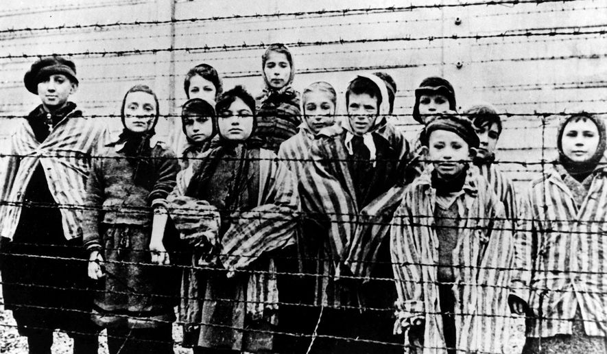 This file photo taken just after the liberation by the Soviet army in January 1945 shows a group of children wearing concentration camp uniforms behind barbed wire fencing in the Oswiecim (Auschwitz) Nazi concentration camp. A 94-year-old former SS guard at the Auschwitz death camp is going on trial Thursday, Feb. 11, 2016, on 170,000 counts of accessory to murder, the first of up to four cases being brought to court this year in an 11th-hour push by German prosecutors to punish Nazi war crimes. (AP Photo)