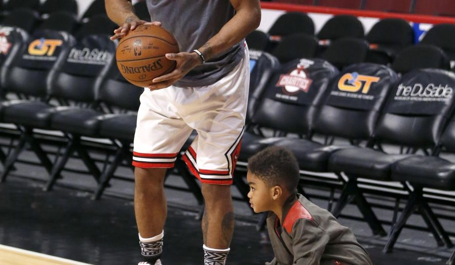 Derrick Rose Jr., right, dribbles next to his father Chicago Bulls' guard Derrick Rose, before an NBA basketball game between the Bulls and Atlanta Hawks Wednesday, Feb. 10, 2016, in Chicago. (AP Photo/Charles Rex Arbogast)