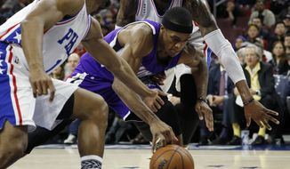 Sacramento Kings' Rajon Rondo, center, chases after a loose ball between Philadelphia 76ers' Ish Smith, left, and Robert Covington during the first half of an NBA basketball game, Wednesday, Feb. 10, 2016, in Philadelphia. (AP Photo/Matt Slocum)