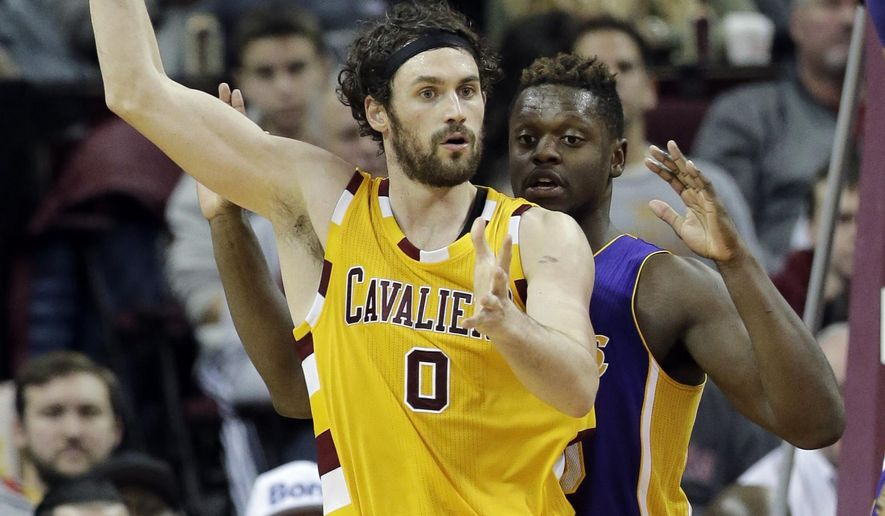 Cleveland Cavaliers' Kevin Love (0) looks to pass around Los Angeles Lakers' Julius Randle (30) in the first half of an NBA basketball game Wednesday, Feb. 10, 2016, in Cleveland. (AP Photo/Tony Dejak)