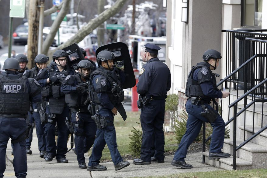 New York City police enter a hotel, Wednesday, Feb. 10, 2016, while searching for a murder suspect in the Staten Island borough of New York. (AP Photo/Seth Wenig)