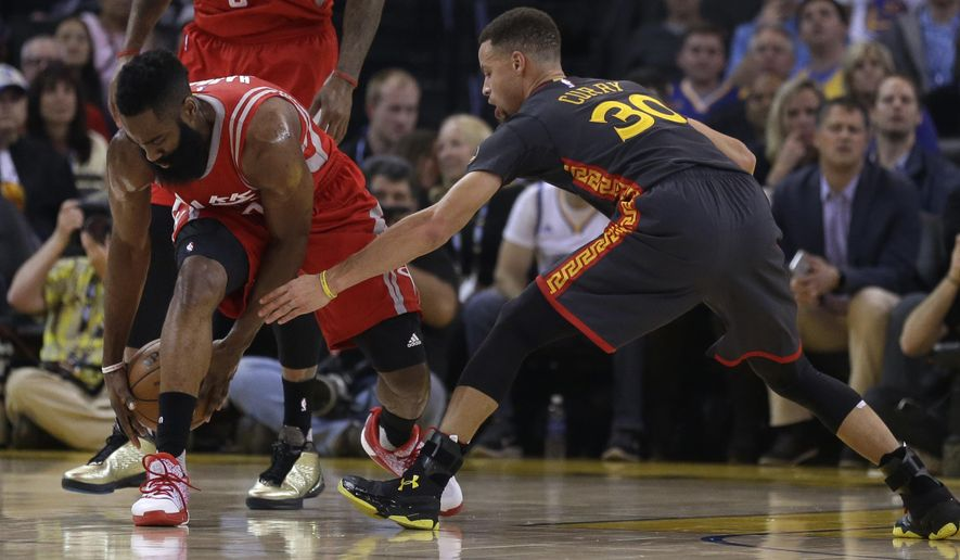 Houston Rockets' James Harden, left, keeps the ball from Golden State Warriors' Stephen Curry (30) during the first half of an NBA basketball game Tuesday, Feb. 9, 2016, in Oakland, Calif. (AP Photo/Ben Margot)