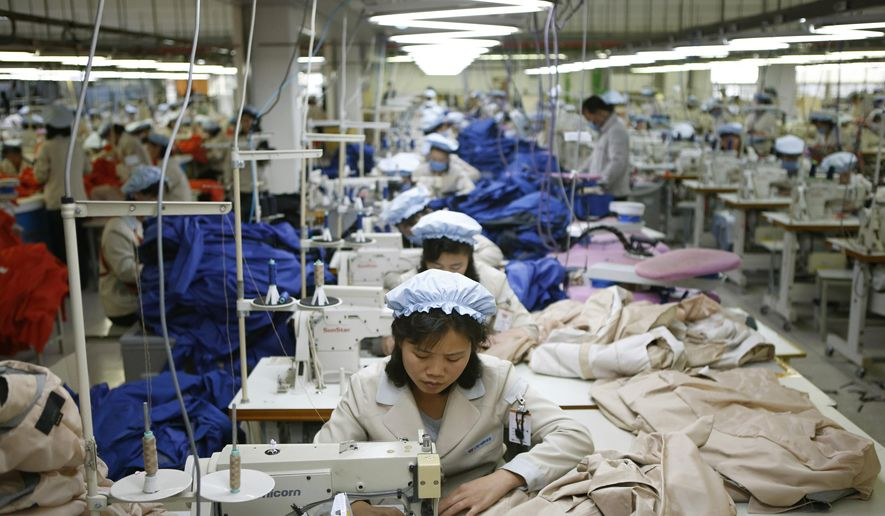 In this Dec. 19, 2013, file photo, North Korean workers assemble jackets at a factory of a South Korean-owned company at the jointly run Kaesong Industrial Complex, in Kaesong, North Korea. South Korea says Wednesday, Feb. 10, 2016, it will halt operations at joint industrial park with North Korea in response to the North's recent rocket launch. (Kim Hong-Ji/Pool Photo via AP, File)