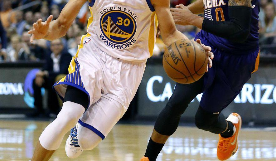 Golden State Warriors' Stephen Curry (30) drives past Phoenix Suns' Orlando Johnson during the first half of an NBA basketball game Wednesday, Feb. 10, 2016, in Phoenix. (AP Photo/Matt York)