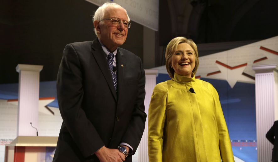 Democratic presidential candidates Sen. Bernard Sanders of Vermont and Hillary Clinton smile as they take the stage before a Democratic presidential primary debate at the University of Wisconsin-Milwaukee on Thursday. (Associated Press)