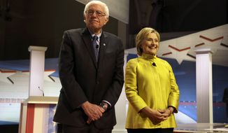 Democratic presidential candidates Sen. Bernard Sanders of Vermont and Hillary Clinton take the stage before a Democratic presidential primary debate at the University of Wisconsin-Milwaukee on Thursday. (Associated Press)
