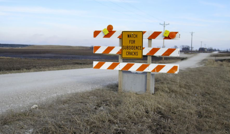 In this Feb. 5, 2016 photo, a traffic sign near the Deer Run coal mine near Hillsboro in southern Illinois warns motorists to be aware of cracks in the road caused by settling of the ground from mining, a process known as subsidence. Mine owner Peabody Energy is asking state regulators to approve a 7,731-acre expansion that is opposed by some residents who fear it could jeopardize public health and cause environmental damage. A smoldering underground fire has led the company to idle its operations (AP Photo/Alan Scher Zagier)