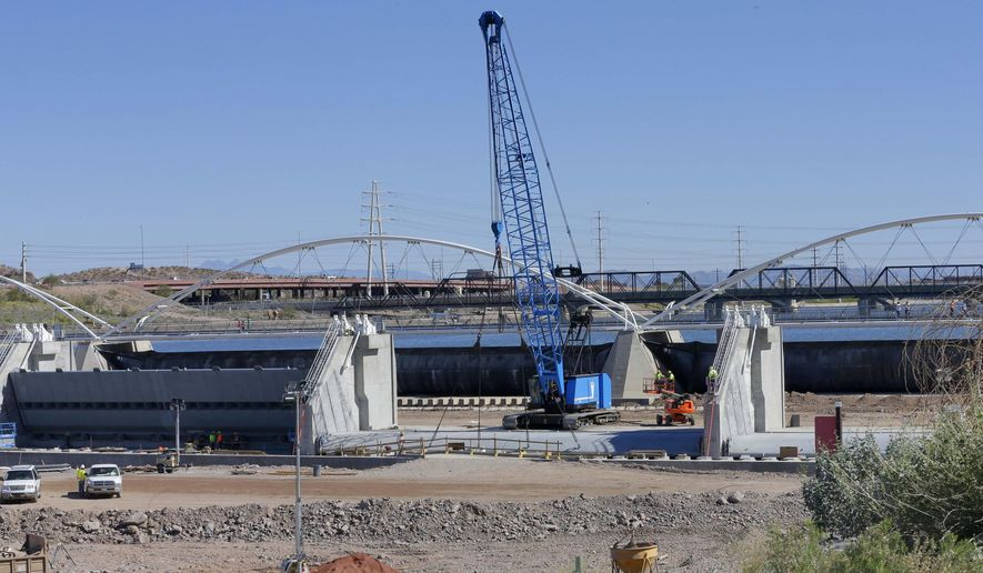 The inflatable dam holding back the Tempe Town Lake waters stretches across the lake as crews work in the Salt River to prepare a new dam, Thursday, Feb. 11, 2016 in Tempe, Ariz. The 16-year-old manmade lake that transformed a 2-mile stretch of the normally dry Salt River bed into a place for a recreation and relaxation, is slowly being emptied so its current dam can be replaced with a new one. (AP Photo/Matt York)