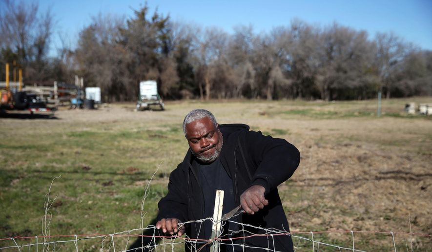 Mark Carter helps to take down an old fence on an 18-acre plot of land donated to Bonton Farms off Seagoville in Dallas, Texas, Wednesday, Feb. 10, 2016. Bonton Farms workers were preparing an entryway and perimeter fencing on the land. Fred Treffinger donated the land to serve as an extension of the current farm operations in the Bonton neighborhood of Dallas. (Andy Jacobsohn/The Dallas Morning News via AP)