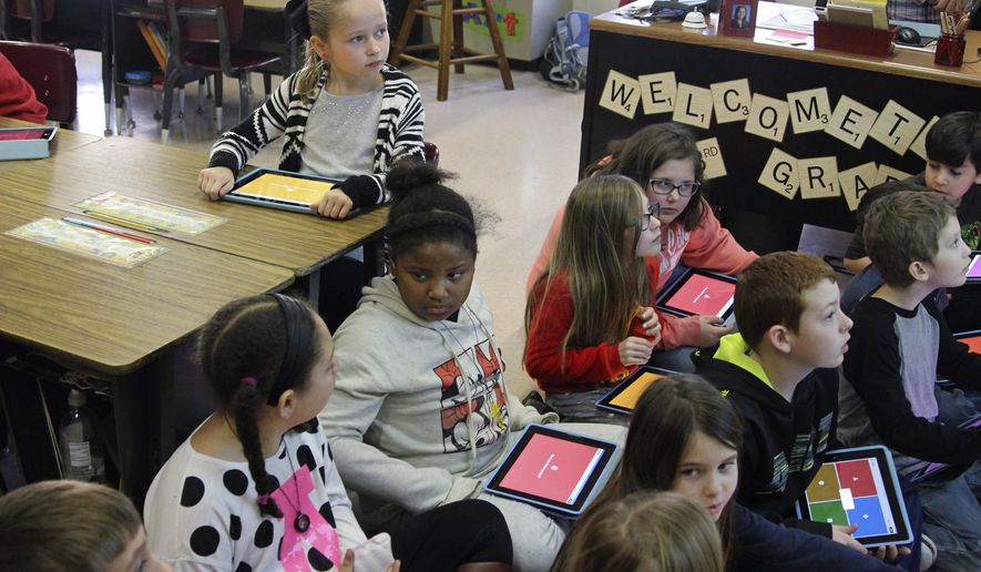 In this Jan. 28, 2016 photo, third-graders at Lincoln Elementary School in Marion, Ill., gather with iPads at the front of the class to complete a review quiz about the Rev. Dr. Martin Luther King, Jr. They are part of a pilot program that supplies iPads to each student in the class. (Sarah Halasz Graham/The Southern via AP)