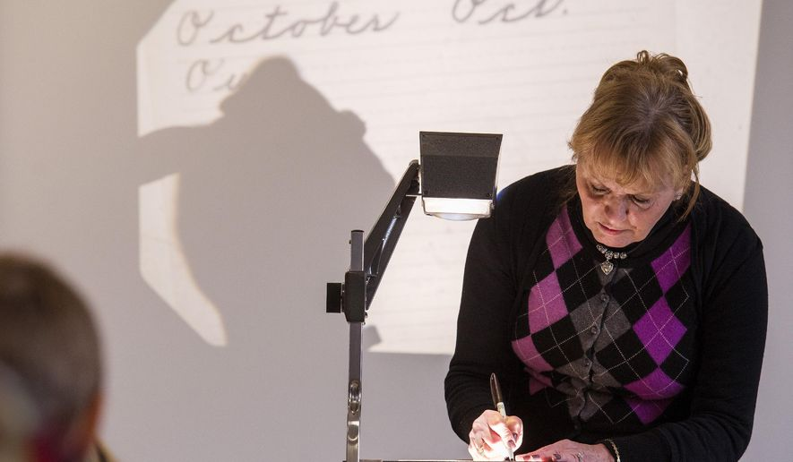 ADVANCE FOR THE WEEKEND OF FEB. 13 - In this Thursday, Jan. 21, 2016 photo, second-grade teacher Roni Albanese uses an overhead projector to display examples of proper cursive handwriting during a lesson at Independence Elementary School in Independence Township, Pa. (Kevin Lorenzi/Beaver County Times via AP) MANDATORY CREDIT