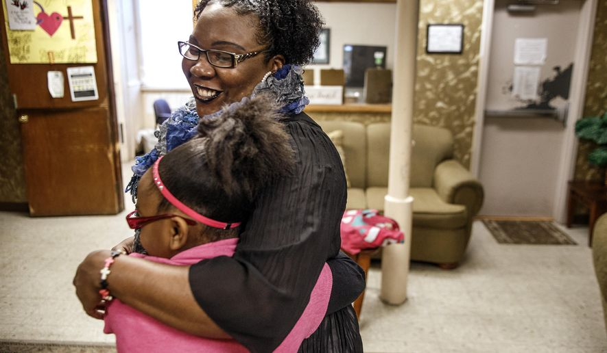 In this Thursday, Jan. 21, 2016 photo, Natasha and her daughter embrace each other before the school bus arrives at the Bethesda Mission Women and Children's Shelter in Harrisburg, Pa. The 10-year-old girl is one of Pennsylvania's roughly 22,000 homeless students in grades pre-K through 12. (Dan Gleiter/PennLive.com via AP)
