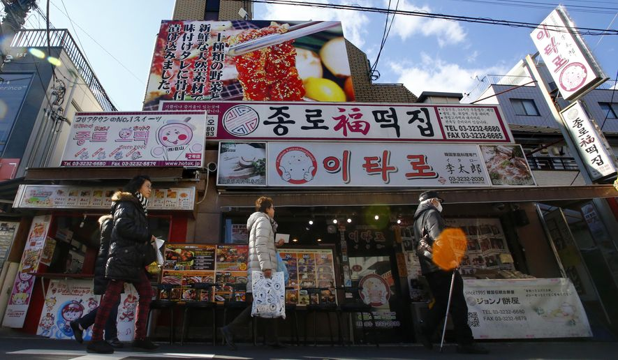 In this Wednesday, Feb. 10, 2016 photo, people walk by a Korean restaurant in Tokyo's Korean district. Japan has a half-million ethnic Korean residents, and the pro-North Korean community is estimated to make up 30,000 to 100,000 of them. Most of them are descendants of Koreans who came to Japan during its 1910-45 colonization of the Korean Peninsula, including those brought here for slave labor at mines and factories in final years of World War II. The Korean communities here are represented by two main groups, one linked to the North and the other to the South. (AP Photo/Shizuo Kambayashi)