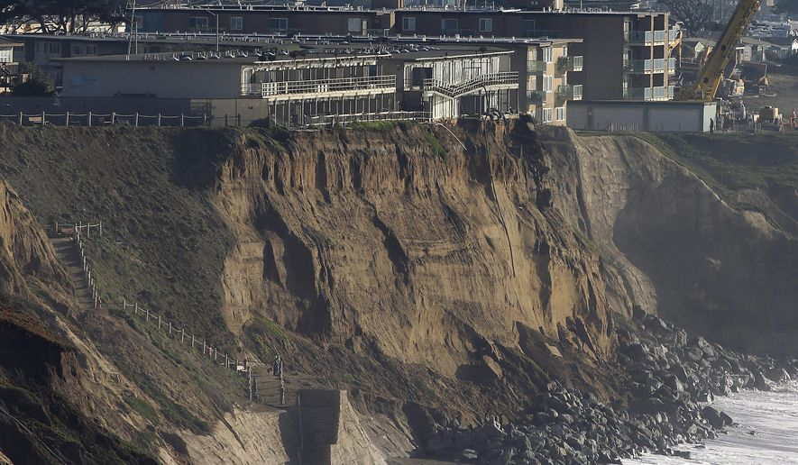 FILE - In this Jan. 27, 2016 file photo, boulders shore up an eroding cliff below an apartment complex that residents were forced to evacuate, at top left, in Pacifica, Calif. Living with the Pacific Ocean as your backyard has its benefits. But the crumbling ocean cliffs have forced dozens to move quickly and at a high cost. (AP Photo/Jeff Chiu, file)