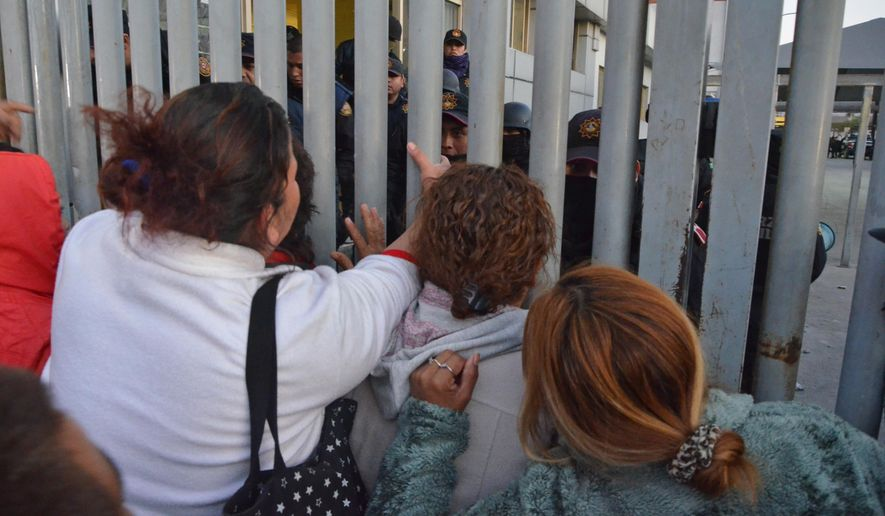Relatives of inmates stand outside the Topo Chico prison facing police, after a riot broke out around midnight, in Monterrey, Mexico, Thursday, Feb. 11, 2016. Dozens of inmates were killed and several injured in a brutal fight between two rival factions at a prison in northern Mexico on Thursday, the state governor said. (AP Photo/Emilio Vazquez)
