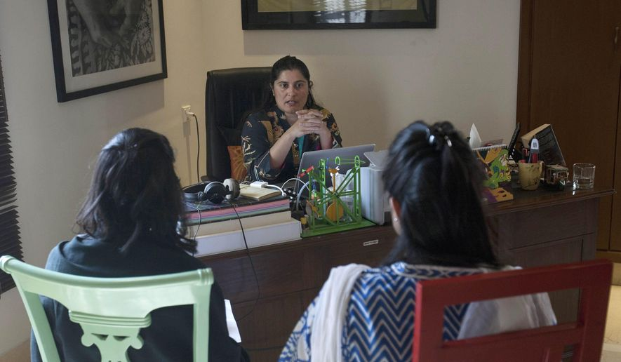 In this Tuesday, Feb. 2, 2016 photo, Pakistan's Oscar winning filmmaker, Sharmeen Obaid-Chinoy discusses with colleagues at her office in Karachi, Pakistan. Obaid-Chinoy is nominated for a second Oscar for her moving story of a teenage girl shot and dumped into a river because she married a man of her choosing. (AP Photo/Shakil Adil)