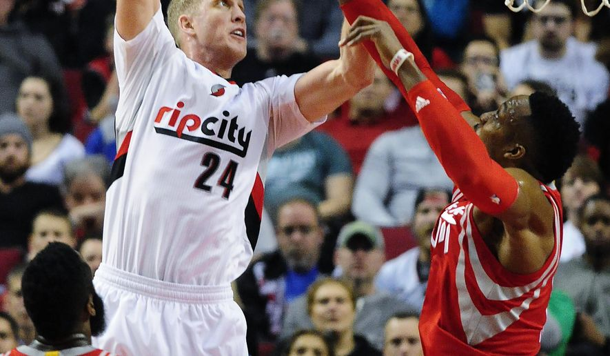 Portland Trail Blazers center Mason Plumlee (24) shoots over Houston Rockets center Dwight Howard, right, as Rockets guard James Harden (13) watches during the first half of an NBA basketball game in Portland, Ore., Wednesday, Feb. 10, 2016. (AP Photo/Steve Dykes)