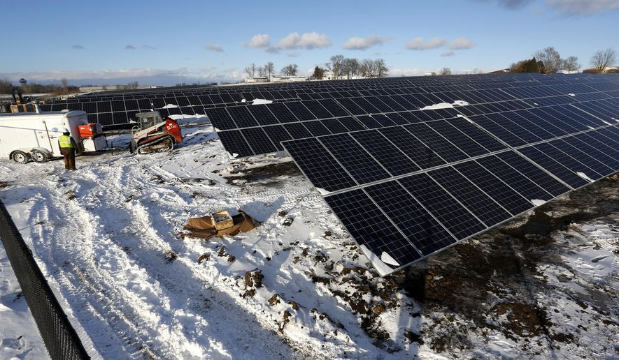 In this photo taken on Jan. 26, 2016, progress continues to be made as the panels are installed for the Cedar Falls Utilities solar garden in the northeast corner of Prairie Lakes Park, in Cedar Falls, Iowa. (Matthew Putney /The Courier via AP) MANDATORY CREDIT