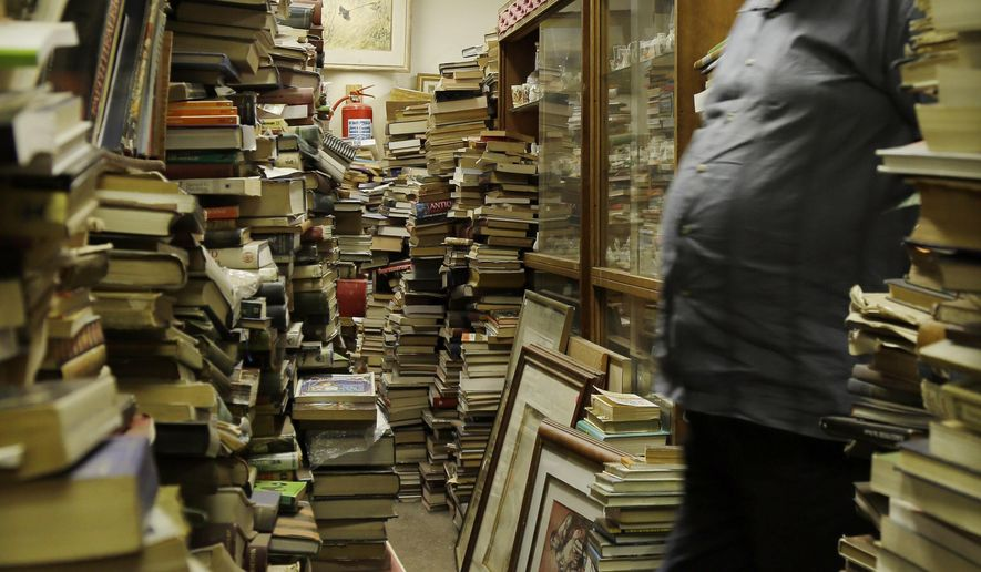 In this photo taken Monday, Feb. 8, 2016 Jonathan Klass, walks out of his office in his bookstore containing some 2 million books and prints in Johannesburg, South Africa. The Collectors Treasury, a three-storey bookshop owned by brothers Jonathan and Geoff Klass, is dedicated to preserving history and nostalgia and contains everything from VHS tapes of classic TV shows to floral porcelain trinkets, but books are prized above all. (AP Photo/Themba Hadebe)