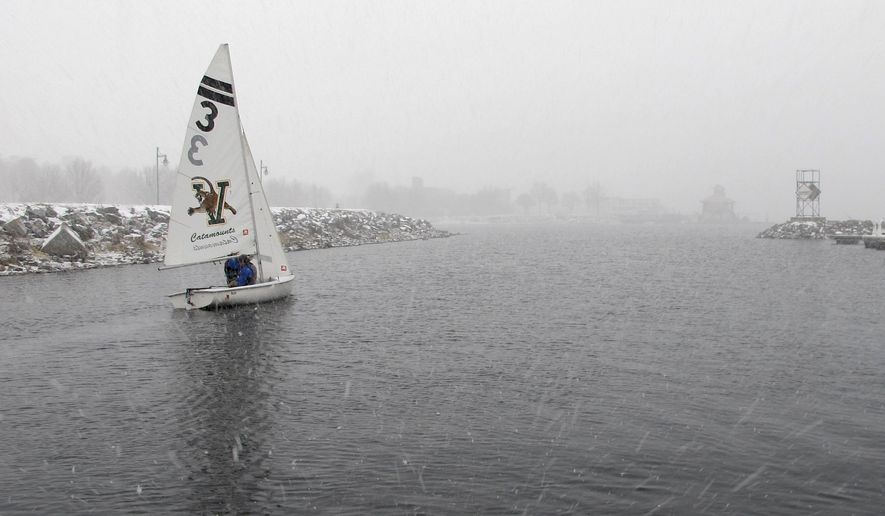 In this Wednesday, Feb. 10, 2016 photo, members of the University of Vermont sailing team set sail during snow squalls on Lake Champlain in Burlington, Vt. The team normally has to wait for ice on the lake to thaw in March or April to start practices. This year's unusual winter with little snow and spurts of mild temperatures has thus far prevented the open lake from freezing. Their coach decided to take advantage of that and get in some winter practices on the chilly lake. (AP Photo/Lisa Rathke)