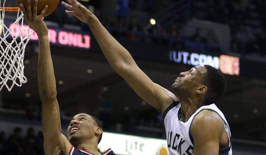 Washington Wizards' Otto Porter Jr. (22) goes up for a shot against Milwaukee Bucks' Jabari Parker (12) during the first half of an NBA basketball game Thursday, Feb. 11, 2016, in Milwaukee. (AP Photo/Aaron Gash)