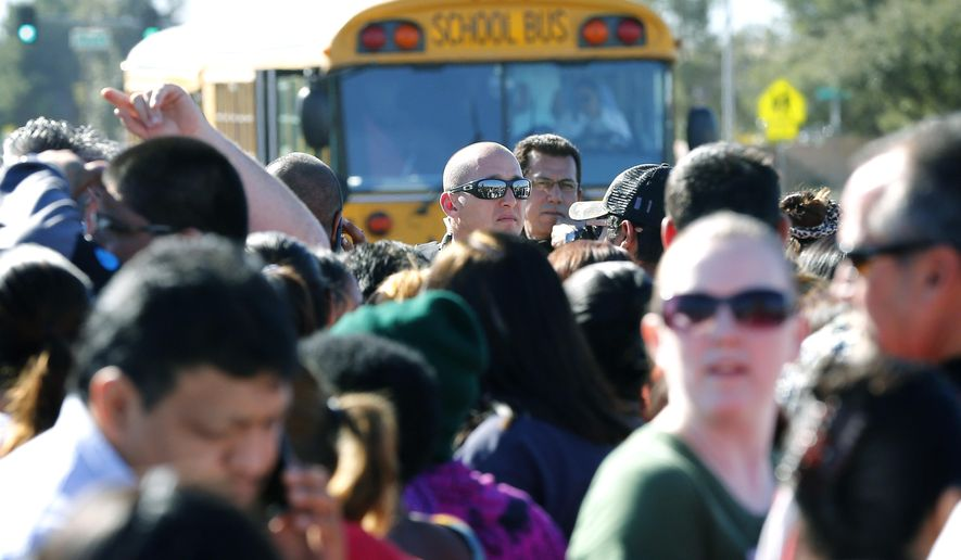A Phoenix police officer, center, tries to give instructions to parents waiting to board buses to reunite with their children, Friday, Feb. 12, 2016, in Glendale, Ariz., after two students died in a shooting at Independence High School in the Phoenix suburb. The danger at the campus was over, police said, as worried parents crowded stores nearby to await word on their children.(AP Photo/Matt York)