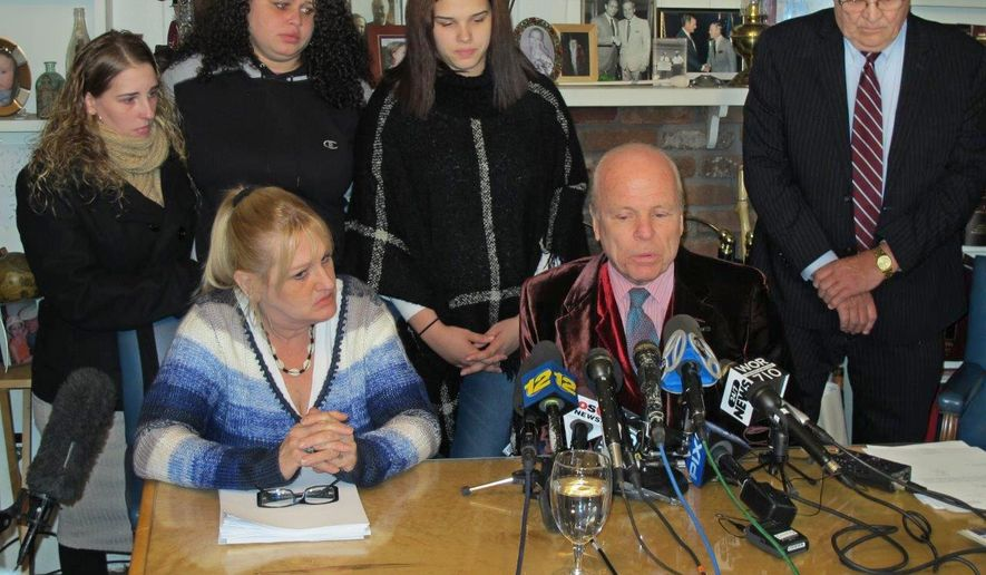 "Attorney John Ray, seated, speaks at a press conference at his office in Miller Place, N.Y., on Friday, Feb. 12, 2016. Ray represents the family of Shannan Gilbert, a Jersey City, N.J., prostitute whose remains were found near where police discovered the bodies of 10 other slain people in the notorious ""Long Island serial killer"" case. Ray says a new autopsy suggests Gilbert may have been strangled. At Ray's right is Mari Gilbert, Shannan Gilbert's mother. Standing, from left, are Gilbert's sisters, Stevie Smith, Sarra Gilbert, and Sherre Gilbert. Retired police detective William Mahoney is at right. (AP Photo/Frank Eltman)"