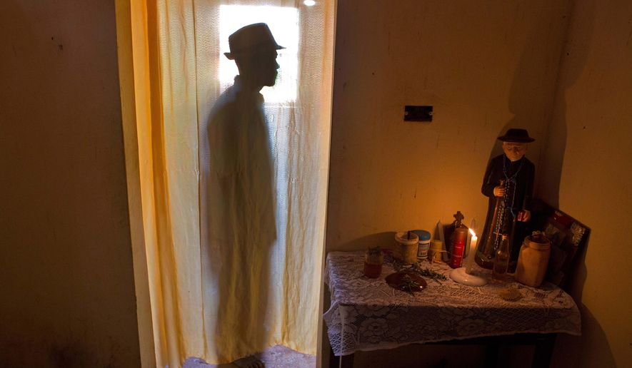 """In this Feb. 2, 2016 photo, Jose Esteves, 63, stands next to his statue of """"Padre Cicero"""" as he prepares spiritually for Carnival celebrations inside his home in Nazare da Mata, Brazil. Padre Cicero is venerated here as a saint but not recognized as one by the Roman Catholic Church. (AP Photo/Eraldo Peres)"""