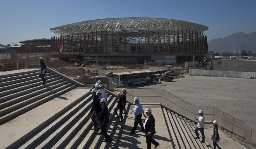 FILE - In this June 11, 2015, file photo, the Arena Carioca 1 is seen in the background as officials visit the Olympic Park of the 2016 Olympics in Rio de Janeiro, Brazil. Hundreds of thousands of foreign visitors are expected for the Olympics, which open Aug. 5. 2016. But there are growing concerns that some may stay away, frightened off by the mosquito-borne virus that is being linked to severe birth defects. (AP Photo/Felipe Dana, File)