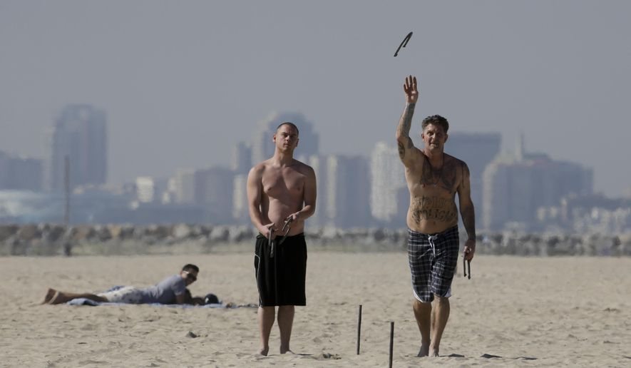 Two beach goers play horse shoes in the sand, Friday, Feb. 12, 2016, in Seal Beach, Calif. Ten days with record heat and no rain have Californians worrying about the drought again. (AP Photo/Chris Carlson)
