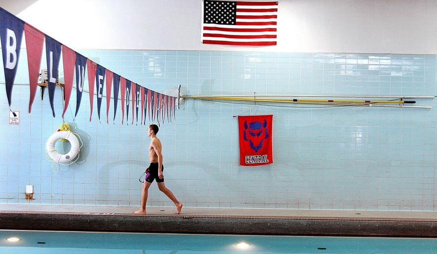 A member of  Davenport Central High School swim team walks towards the locker room after the final practice at this pool in Davenport, Iowa Thursday, Feb. 11, 2016. The facility, which opened in 1960, will be replaced with a modern 8-lane pool as part of extensive renovations to the 110-year-old school. (Jeff Cook/Quad City Times via AP) MANDATORY CREDIT