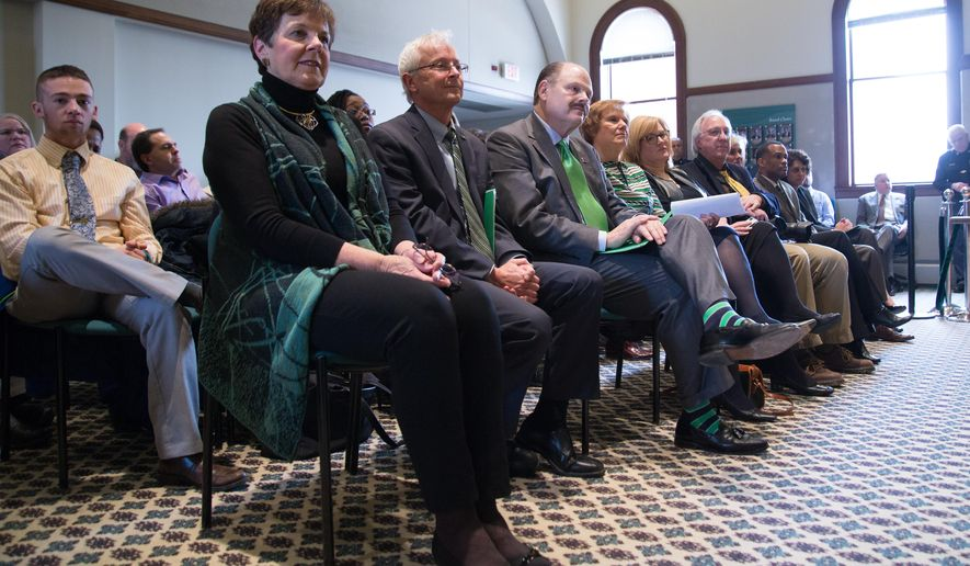 Dr. James M. Smith sits with his wife during the announcement of his appointment as Eastern Michigan University president in Welch Hall at Eastern Michigan University on Friday, Feb. 12, 2016, in Ypsilanti, Mich. (Jenna VonHofe/The Ann Arbor News via AP)