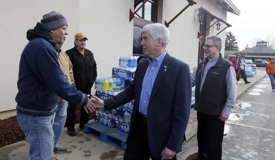 In a file photo from Feb. 5, 2016, Michigan Gov. Rick Snyder, center and Our Lady of Guadalupe Church Deacon Omar Odette, right, meet with volunteers helping to load vehicles with bottled water in Flint, Mich. (AP Photo/Carlos Osorio) ** FILE **