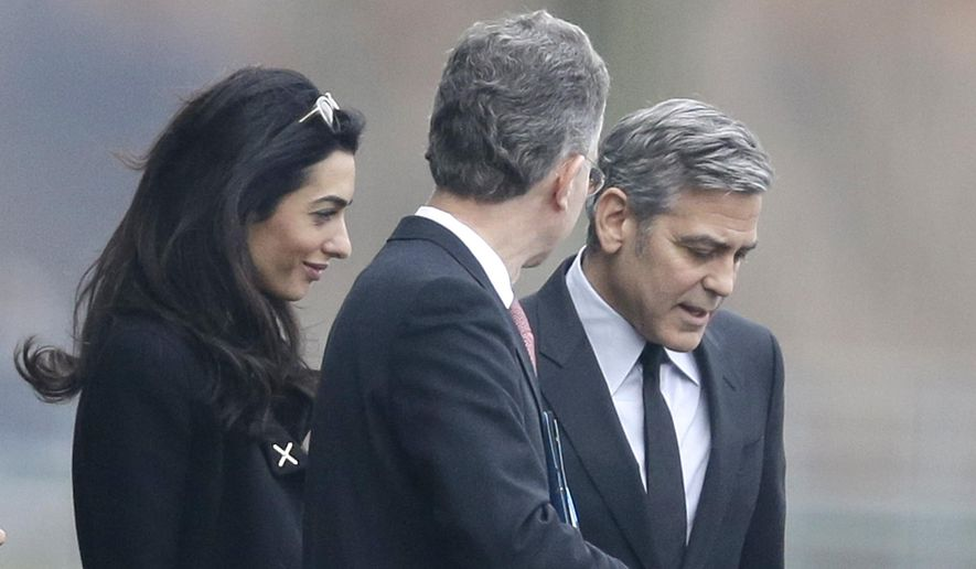 US actor George Clooney, right, and his wife Amal Clooney, left, are accompanied by Merkel's foreign policy advisor Christoph Heusgen as they leave chancellery after private meeting with German chancellor Angela Merkel in Berlin, Germany, Friday, Feb. 12, 2016. (AP Photo/Markus Schreiber)