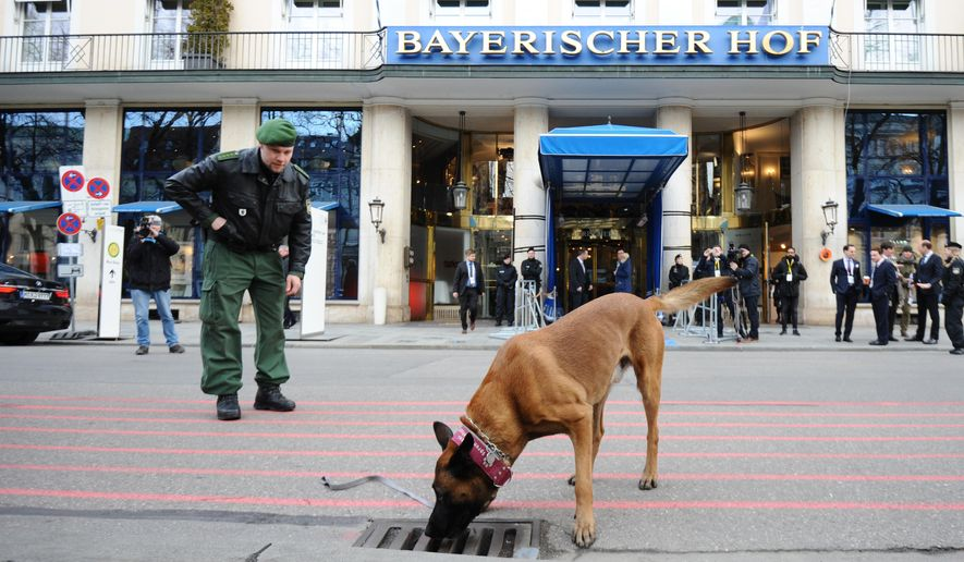 A German policeman inspects the area around the international security conference with a sniffer dog in Munich, southern Germany, Friday, Feb. 12, 2016. The Munich Security Conference, an annual gathering of foreign and defense policy leaders, opens Friday and lasts until Sunday. (Andreas Gebert/dpa via AP)