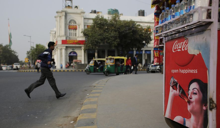 An Indian pedestrian crosses a road near roadside kiosk with a Coca-cola advertisement in New Delhi, India, Friday, Feb. 12, 2016. Coca-Cola suspended bottling at three plants in India, including one in the parched northwest where farmers have been protesting the company's use of dwindling groundwater reserves. (AP Photo/Altaf Qadri)