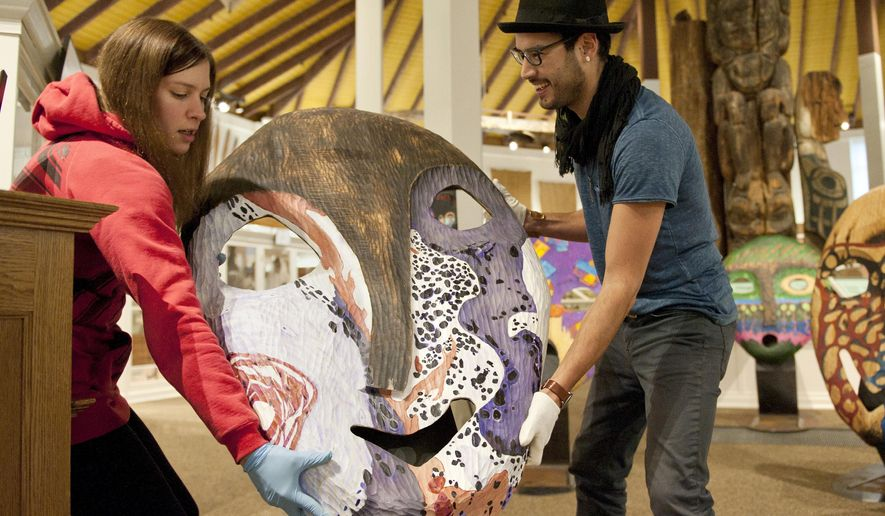 ADVANCE FOR WEEKEND USE FEB 13-14, 2016 AND THEREAFTER - In this Feb. 4, 2016 photo, Sheldon Jackson Museum curator of collections Jackie Fernandez, left, and Eagle River artist Drew Michael place one of Michael's giant masks on a a stand in the museum in Sitka, Alaska. Michael has made a career for himself in the carving trade, showing and selling his work, giving talks at various venues, and teaching at schools around the state. (James Poulson/Daily Sitka Sentinel via AP)  MANDATORY CREDIT