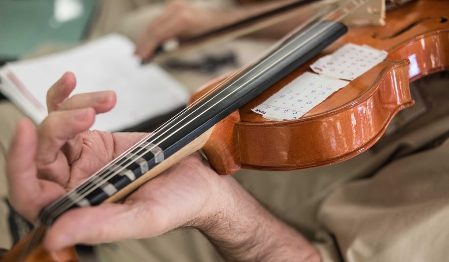 An inmate practices the violin during a music workshop at the Lee Correctional Institution in Bishopville, S.C., Tuesday, Feb. 9, 2016. After a weeklong workshop with the Decoda chamber ensemble, several dozen inmates will perform original music in a concert for the larger incarcerated community, staff, officers, and local and state officials. (AP Photo/Sean Rayford)