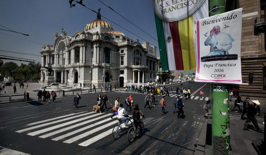 Images welcoming Pope Francis hang from street posts near the Fine Arts Palace in downtown Mexico City, Thursday, Feb. 11, 2016. The pontiff arrives in Mexico on Friday for a week-long visit. (AP Photo/Marco Ugarte)