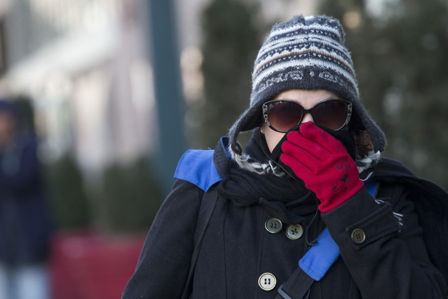 A woman lifts her scarf up in front of her nose to shield from the cold air, Friday, Feb. 12, 2016, in New York. The National Weather Service predicts temperatures well below freezing on Saturday for New York. But wind chills could drop even lower, and wind gusts could reach around 44 mph. (AP Photo/Mary Altaffer)