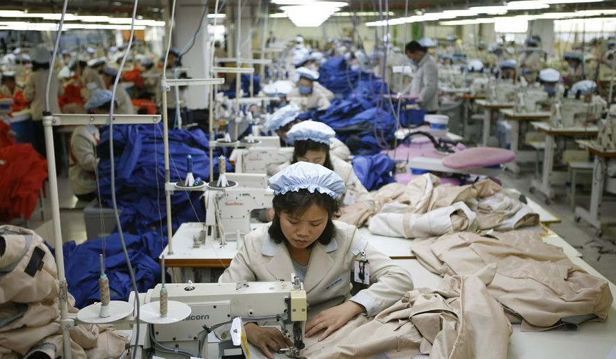 FILE - In this Dec. 19, 2013, file photo, North Korean workers assemble jackets at a factory of a South Korean-owned company at the jointly-run Kaesong Industrial Complex, in Kaesong, North Korea. The closure of a factory park in North Korea jointly run by both Koreas has robbed the impoverished North of a rare source of legitimate hard currency.  (Kim Hong-Ji/Pool Photo via AP, File)
