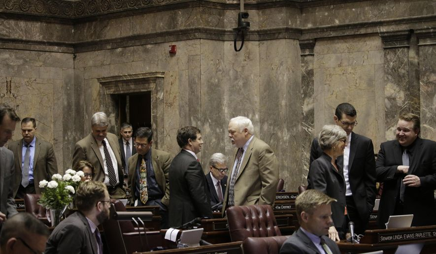 Lawmakers stand on the Senate floor as votes are counted on a constitutional amendment related to raising the legislative voting threshold needed to raise taxes, Friday, Feb. 12, 2016 in Olympia, Wash. The measure, which required a two-thirds majority to pass, failed to get the necessary votes. (AP Photo/Rachel La Corte)