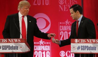 Republican presidential candidate, Sen. Marco Rubio, R-Fla., right, hands Republican presidential candidate, businessman Donald Trump  a tic tac container at a break during the CBS News Republican presidential debate at the Peace Center, Saturday, Feb. 13, 2016, in Greenville, S.C. (AP Photo/John Bazemore) ** FILE **