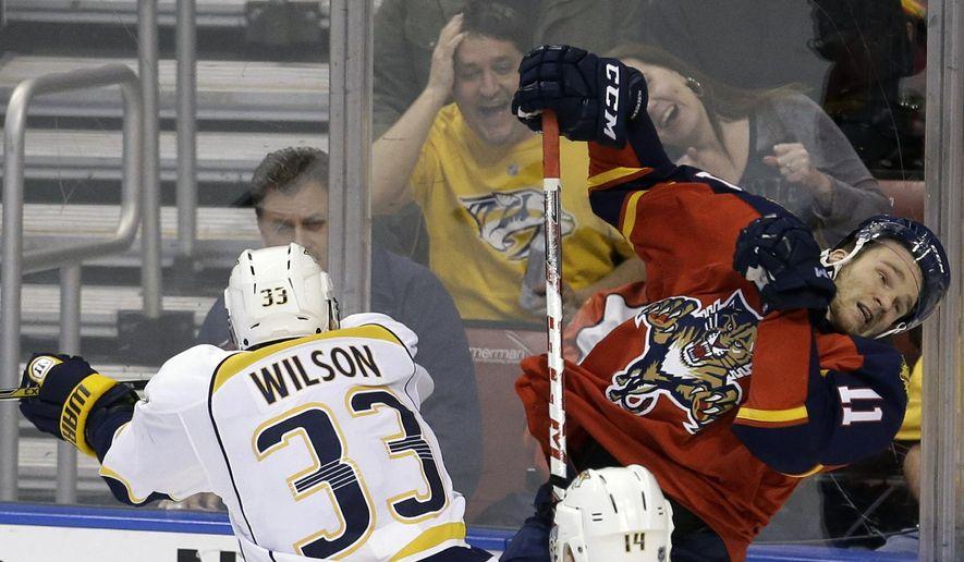 Nashville Predators center Colin Wilson (33) checks Florida Panthers center Jonathan Huberdeau (11) during the second period of an NHL hockey game, Saturday, Feb. 13, 2016, in Sunrise, Fla. (AP Photo/Alan Diaz)