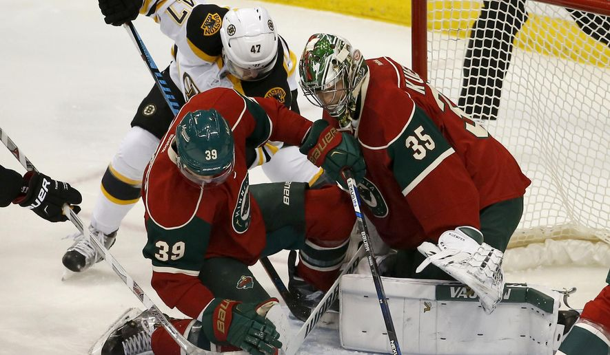 Minnesota Wild defenseman Nate Prosser (39) and Boston Bruins defenseman Torey Krug (47) battle for the puck as Wild goalie Darcy Kuemper (35) covers the net during the first period of an NHL hockey game in St. Paul, Minn., Saturday, Feb. 13, 2016. (AP Photo/Ann Heisenfelt)